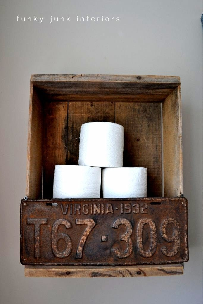 A simple crate and rusty license plate combine to offer toilet paper storage.